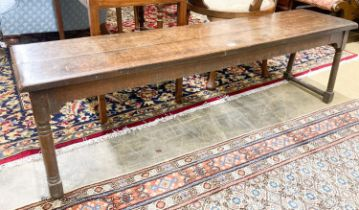 An 18th century style oak low bench seat, length 140cm, depth 32cm, height 42cm
