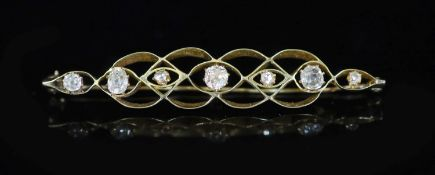 A gold and seven stone graduated rose and old mine cut diamond set bar brooch,67mm, gross 6.8