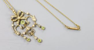 An Art Nouveau 9ct, peridot and seed pearl set scroll pendant, 46mm, gross 3.4 grams, on a gilt