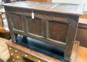 A 17th century caved panelled oak coffer, W.110cm D.48cm H.67cm