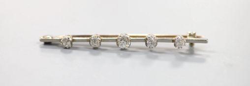 A yellow metal and graduated five stone diamond set bar brooch, 50mm, gross weight 3.7 grams.