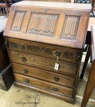 A reproduction oak linenfold carved bureau, W.75cm D.48cm H.99cm