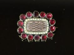 A 19th century gold plated, garnet and seed pearl set mourning brooch,with plaited hair beneath a