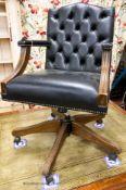 A reproduction beech buttoned blue leather swivel desk chair, W.54cm. D.61cm H.99cm