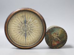 A 19th century circular papier mache box and cover decorated with cherubs and a compass from a
