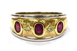 A RUBY THREE STONE 18CT YELLOW AND WHITE GOLD BAND RING with two small round cut diamonds between,