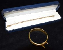 A ROLLED GOLD HINGED BANGLE OF HOLLOW CONSTRUCTION with fern and flower head design, marked inside
