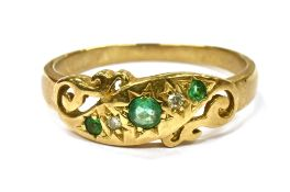 A 9CT GOLD SMALL EMERALD SET DRESS RING the scroll work front diagonally set with three very small