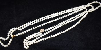 A THREE ROW CULTURED PEARL NECKLACE with a 14ct yellow gold clasp, the uniform round to off round