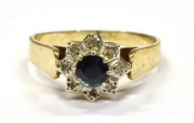 A 9CT GOLD SMALL SAPPHIRE AND DIAMOND CLUSTER RING the central round sapphire with small illusion
