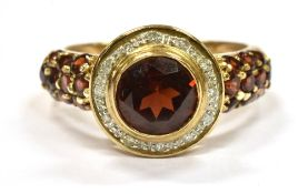 A 9CT GOLD GARNET AND SMALL DIAMOND CLUSTER RING with garnet set shoulders, the central round cut
