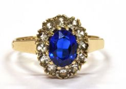 A 9CT GOLD BLUE AND WHITE STONE OVAL CLUSTER RING the central synthetic blue spinel surrounded by