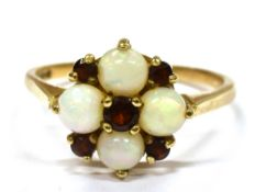 AN OPAL AND GARNET CLUSTER 9CT GOLD DRESS RING the cluster comprising four round white opals and
