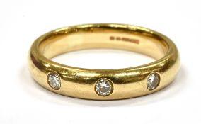 A DIAMOND SET 9CT GOLD WEDDING BAND the plain yellow gold band flush set with three small round