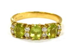 AN 18CT GOLD PERIDOT THREE STONE RING with pairs of small diamonds between, the three oval cut