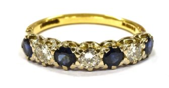 A DIAMOND AND SAPPHIRE SIX STONE GOLD RING comprising three round brilliant cut diamonds, a total