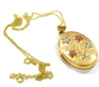 A MODERN 9CT GOLD OVAL LOCKET AND CHAIN the embossed flower spray to the front with red and white
