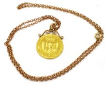 A GEORGE III GOLD GUINEA PENDANT on a long chain, the gold guinea dated 1788 with soldered, scroll