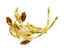 AN 18CT GOLD GARNET SET SPRAY BROOCH the spray of stylised design, set with three marquise cut