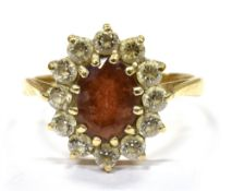 A GARNET AND WHITE CUBIC ZIRCONIA SET OVAL CLUSTER RING the central garnet approx. 8 x 6mm, claw
