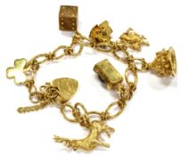 A 9CT GOLD CHARM BRACELET with padlock fastener and seven assorted charms, the padlock fastener