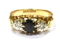 A 9CT GOLD SAPPHIRE AND DIAMOND THREE STONE RING the oval mixed cut sapphire 5.5 x 4.5mm with two