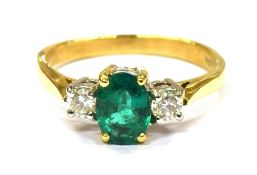 AN EMERALD AND DIAMOND THREE STONE 18CT GOLD RING the central oval cut emerald approx. 7.1 x 5.