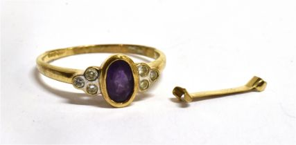 A 9CT GOLD AMETHYST AND WHITE STONE DRESS RING the central oval cut amethyst 6 x 4mm, three white