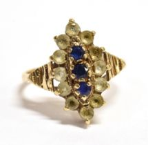 A 9CT GOLD BLUE AND WHITE STONE SET DRESS RING the fancy oval cluster to grooved shoulders and 9ct