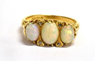 A THREE STONE OPAL 18CT GOLD RING the three oval cabochon cut opals with small diamond points