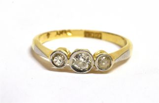 A DIAMOND THREE STONE 18CT RING the three small round cut diamonds rub over set to a 18ct gold