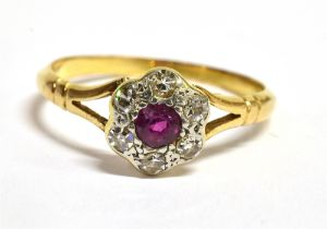 A RUBY AND DIAMOND 18 CT GOLD CLUSTER RING The round cluster comprising a small round cut ruby