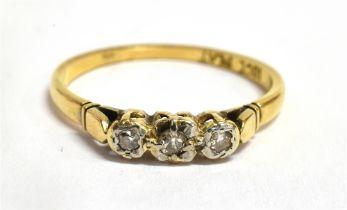 A DIAMOND THREE STONE ILLUSION SET 18CT GOLD RING The three small round eight cut diamonds to