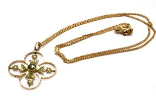 AN EDWARDIAN 9CT GOLD PERIDOT AND SEED PEARL PENDANT On a later 9ct gold chain, the four leaf clover