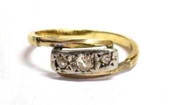 A DIAMOND THREE STONE ILLUSION SET 18 CT GOLD CROSS OVER RING The three small round cut diamonds