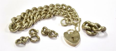 A SILVER CURB LINK BRACELET fitted with a silver heart padlock and safety chain with spare links,