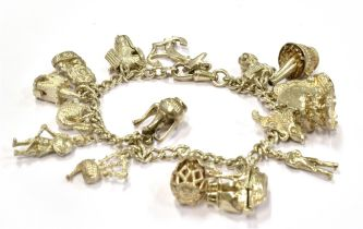 A SILVER AND WHITE METAL CHARM BRACELET weighing 57.6grams