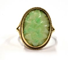A 9CT GOLD JADE (?) STONE COCKTAIL RING With the oval floral carved stone measuring 2cm by 1.5 cm