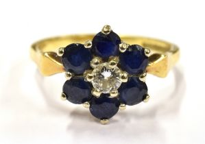 AN 18CT GOLD DIAMOND AND SAPPHIRE SLOWER HEAD RING The central round cut diamond measuring approx.