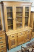 An oak Arts and Crafts bookcase with triple glazed doors over a base with three drawers over a