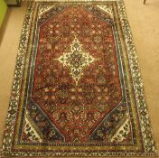 A red ground Sarouk rug with cream central medallion and blue and cream spandrels, 288cm x 186cm