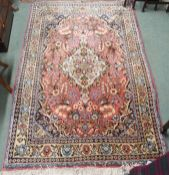 A pink ground Sarough rug with a cream central medallion and floral design, 158cm x 104cm