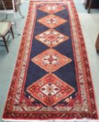 A blue ground Karajeh runner with five central lozenges, 310cm x 118cm Condition Report: Available