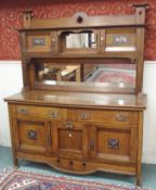 An oak Arts and Crafts sideboard with pierced top rail, mirror and two doors with main mirror on a