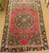 A red ground vintage Tabriz rug with floral medallion design, 282cm x 186cm Condition Report: