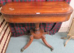 A Victorian mahogany inlaid fold over tea table on pedestal base with sabre legs and hairy paw brass