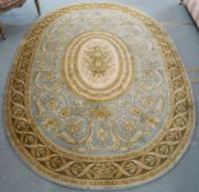A green ground oval wool rug with floral central medallion, 243cm x 168cm, Condition Report: