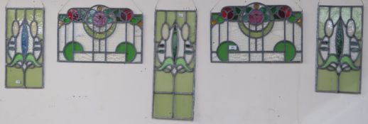 A leaded and stained glass panel, 56cm x 23cm with two matching panels, 43cm x 22cm and a pair of
