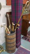 An oak coopered stick stand with various sticks and umbrellas Condition Report: Available upon