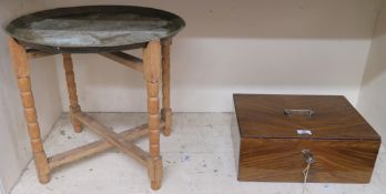 A small metal strong box, 16cm high x 40cm wide x 30cm deep and a brass topped folding table (2)